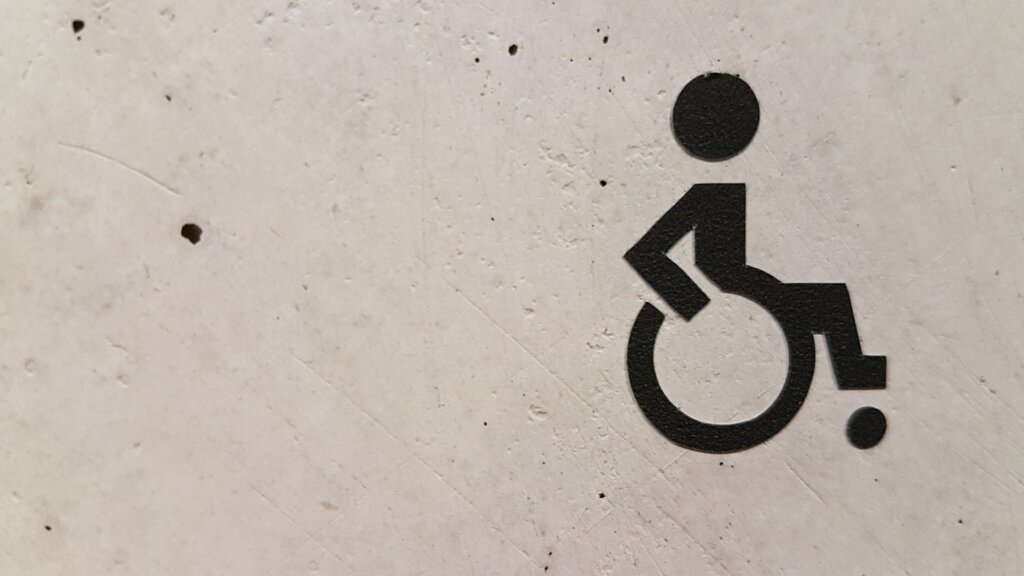black spray painted disability sign on a white concrete wall